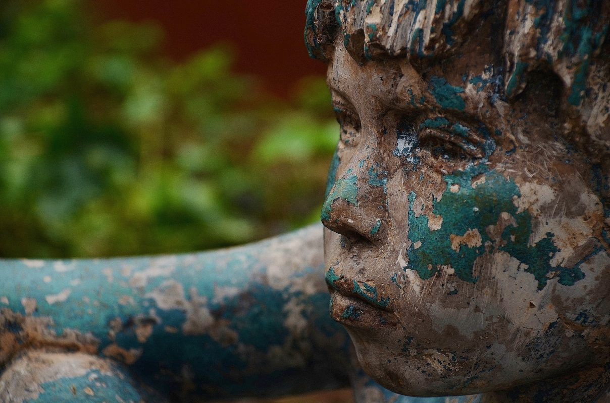 wooden painted sculpture of boy gazing into the distance